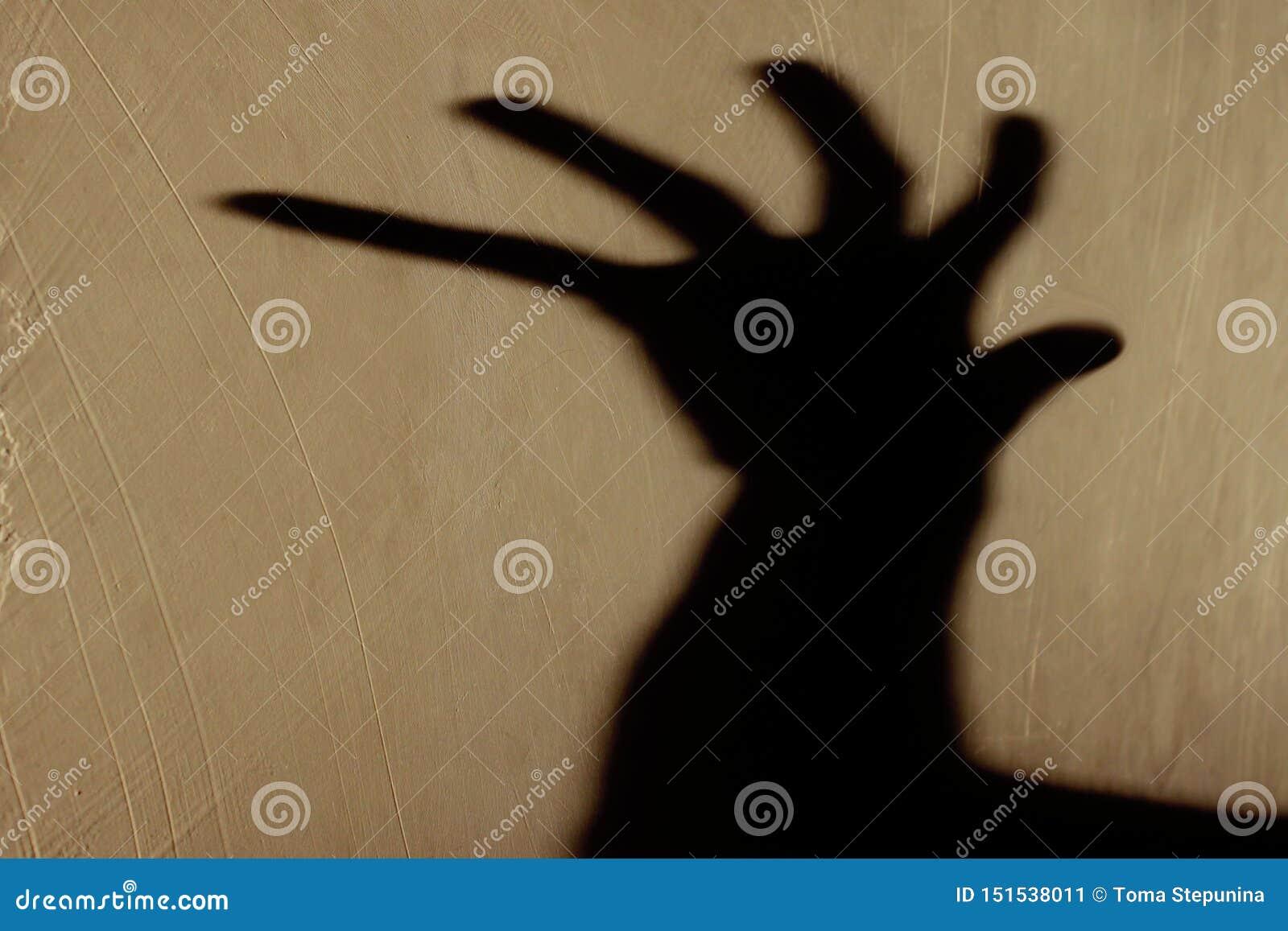 Vreemde Schaduw op de Muur Vreselijke Schaduw abstracte achtergrond Zwarte Schaduw van een Grote Hand op de Muur Silhouet van een