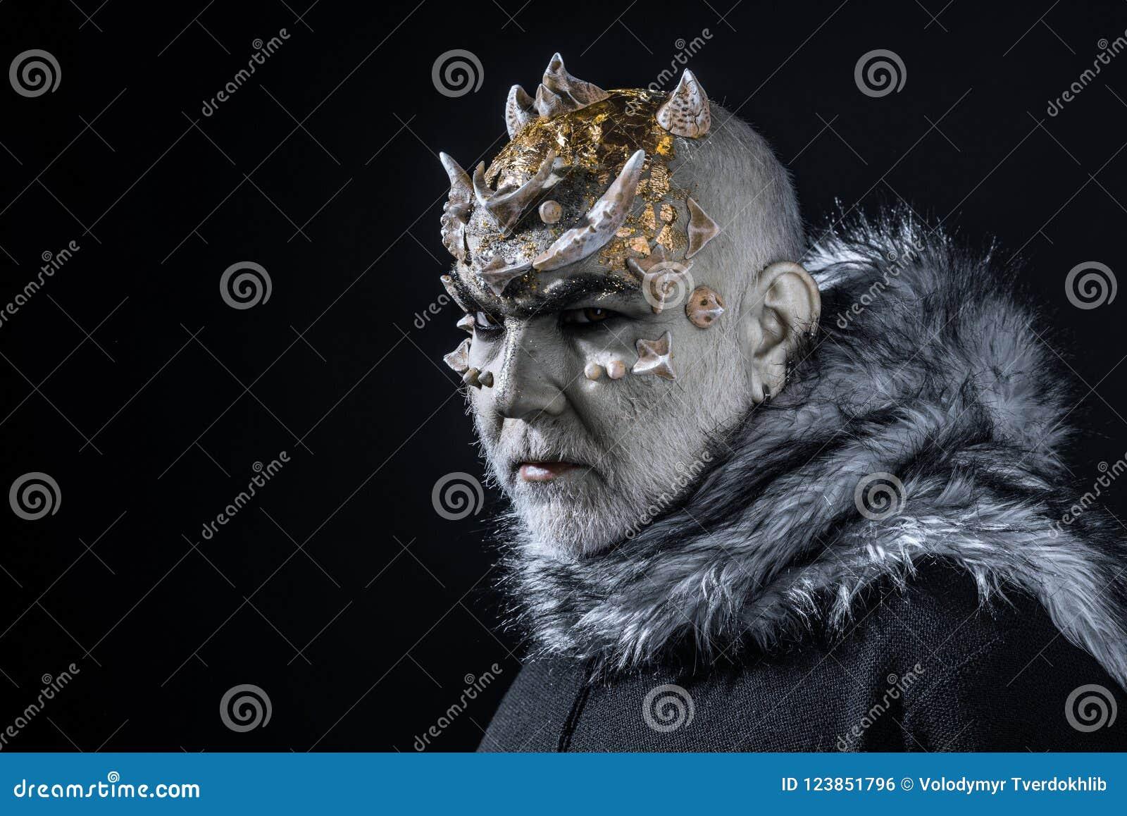 Vreemdeling, demon, tovenaarsmake-up Demon op zwarte achtergrond, exemplaarruimte Mens met doornen of wratten in bontjas theatraa