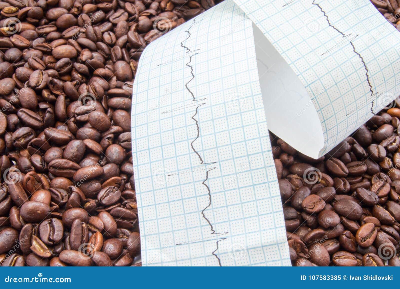 Vriden typ av elektrokardiogrammet med den utskrivavna ECG-linjen ligger på stekte kaffebönor Få effekt kaffe och koffein på hjär