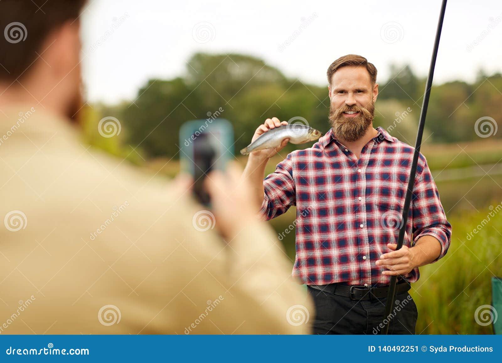 Vriend die visser met vissen fotograferen bij meer