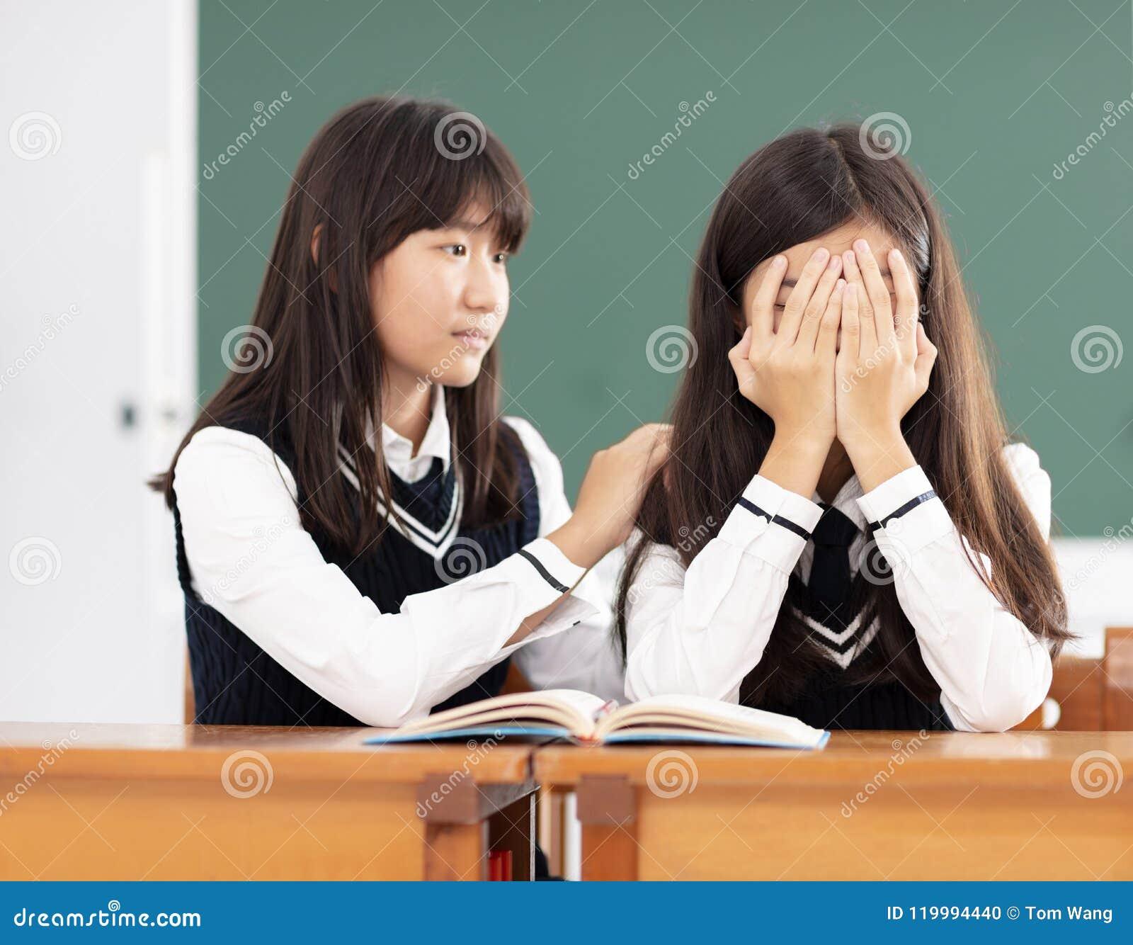 Vriend het troosten aan droevige student in klaslokaal