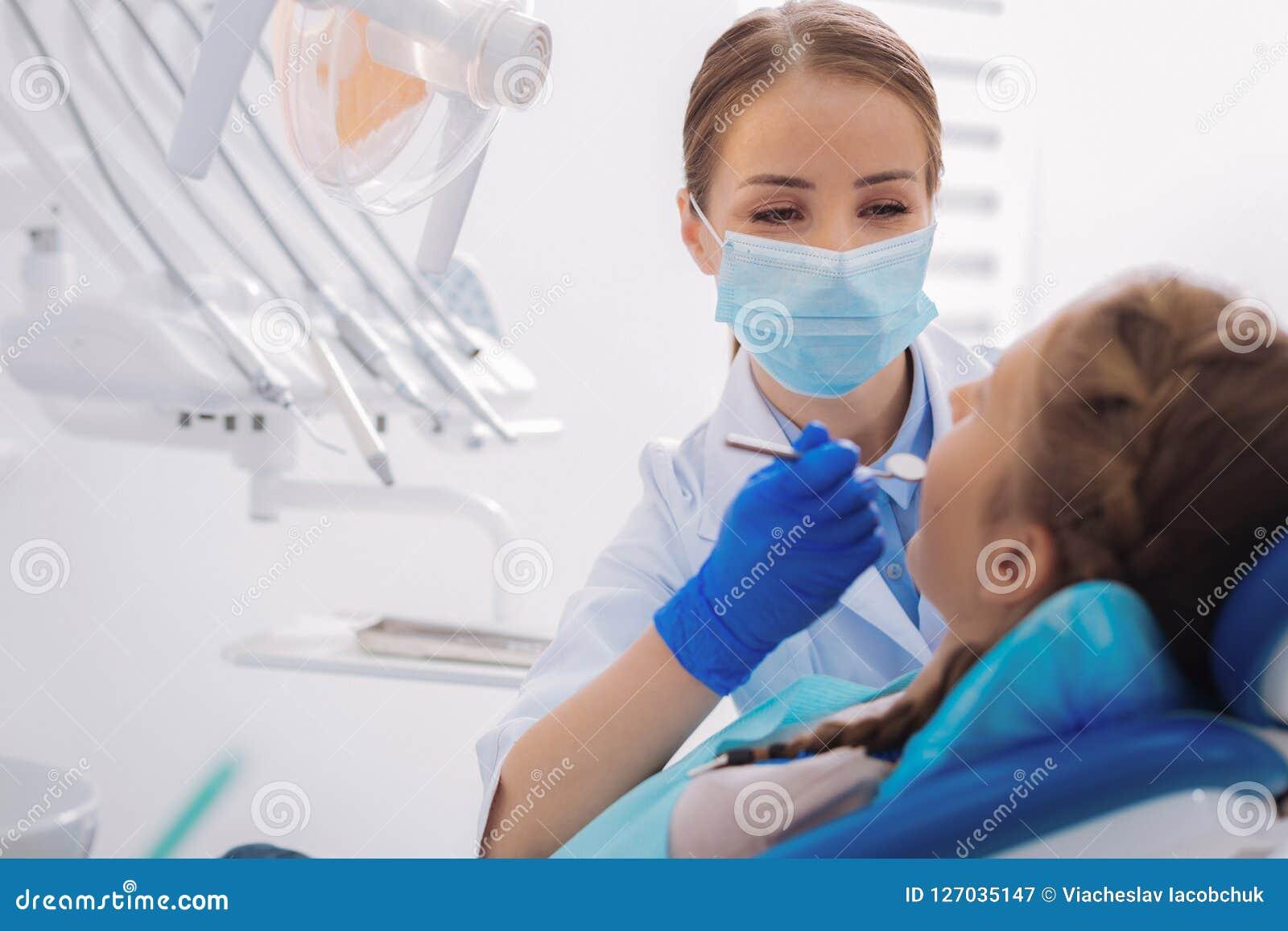 Vriendelijke orthodontist die een tandspiegel houden terwijl het werken