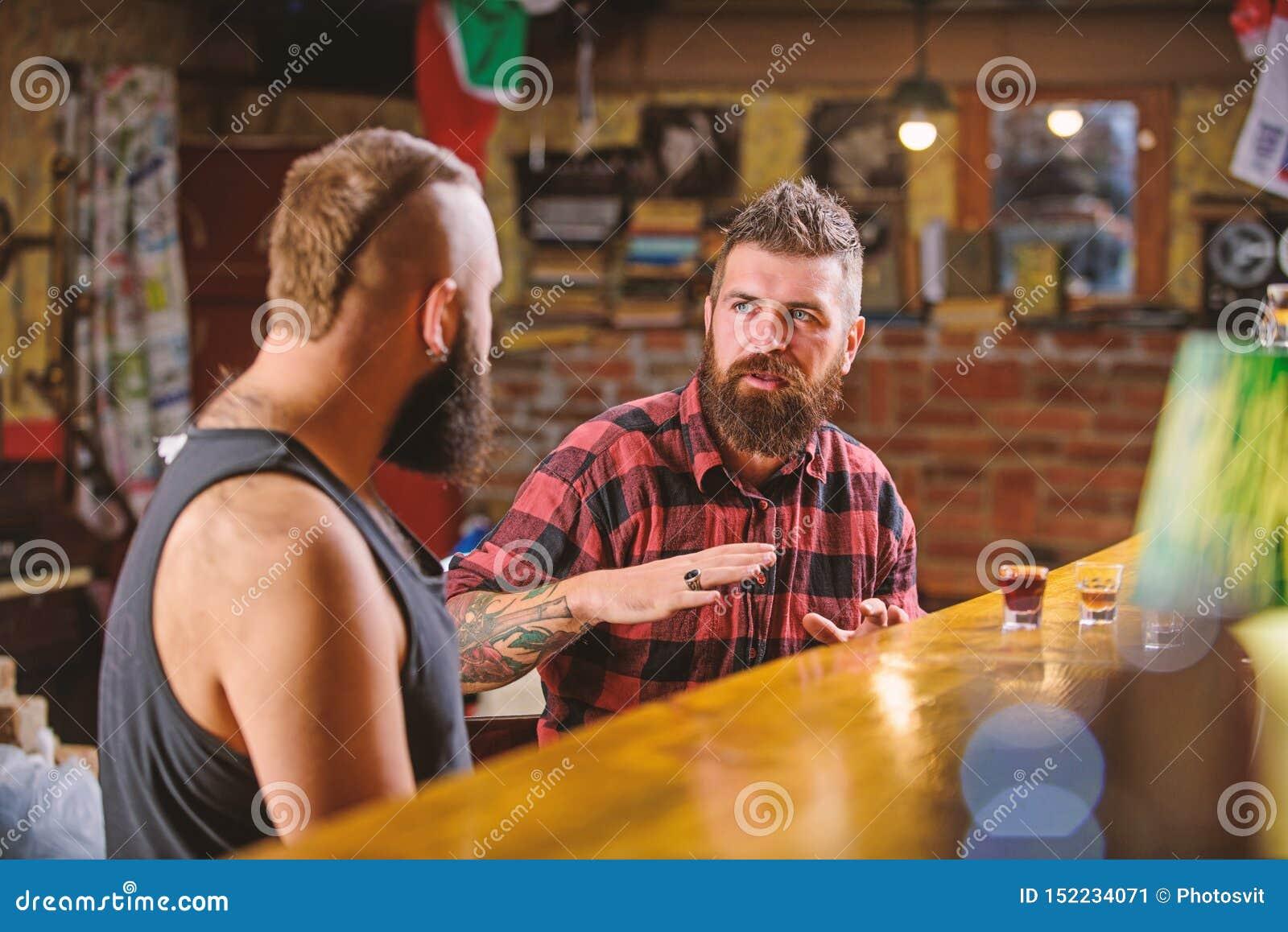 Vrienden die in bar of bar ontspannen Soulmates gedronken gesprek Besteedt de Hipster brutale gebaarde mens vrije tijd met vriend