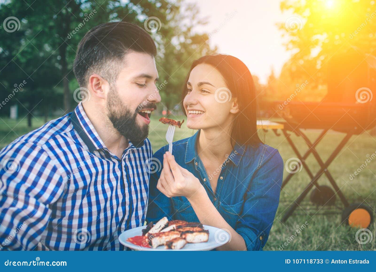 Vrienden die barbecue maken en lunch in de aard hebben Paar die pret hebben terwijl het eten en het drinken bij een Gelukkige pic