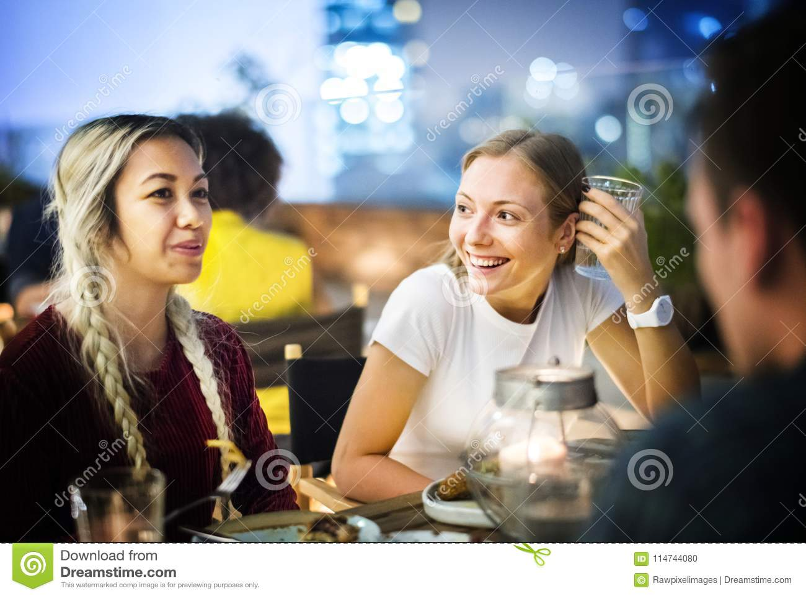 Vrienden die een diner hebben samen bij een dakbar
