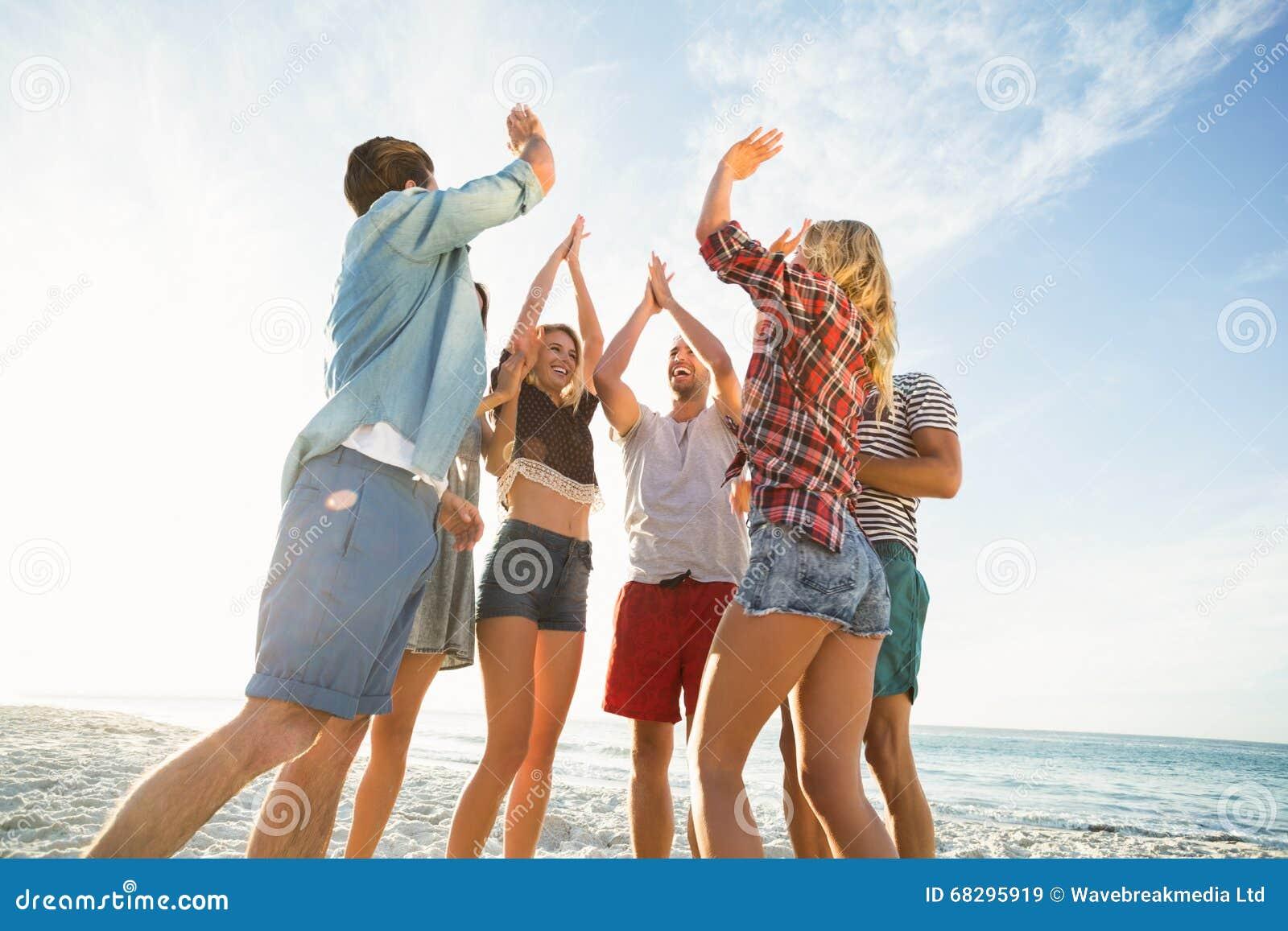 Vrienden die hoogte vijf op het strand doen