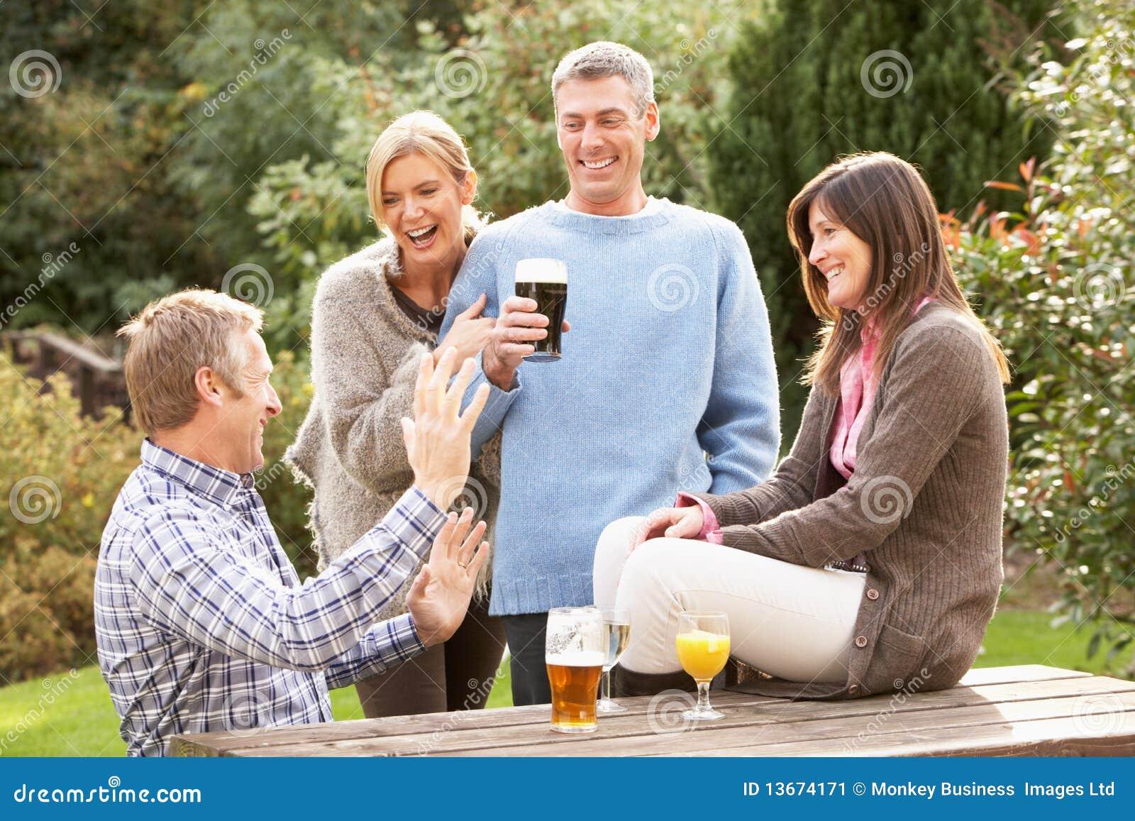 Vrienden die in openlucht van drank in de tuin van de bar genieten
