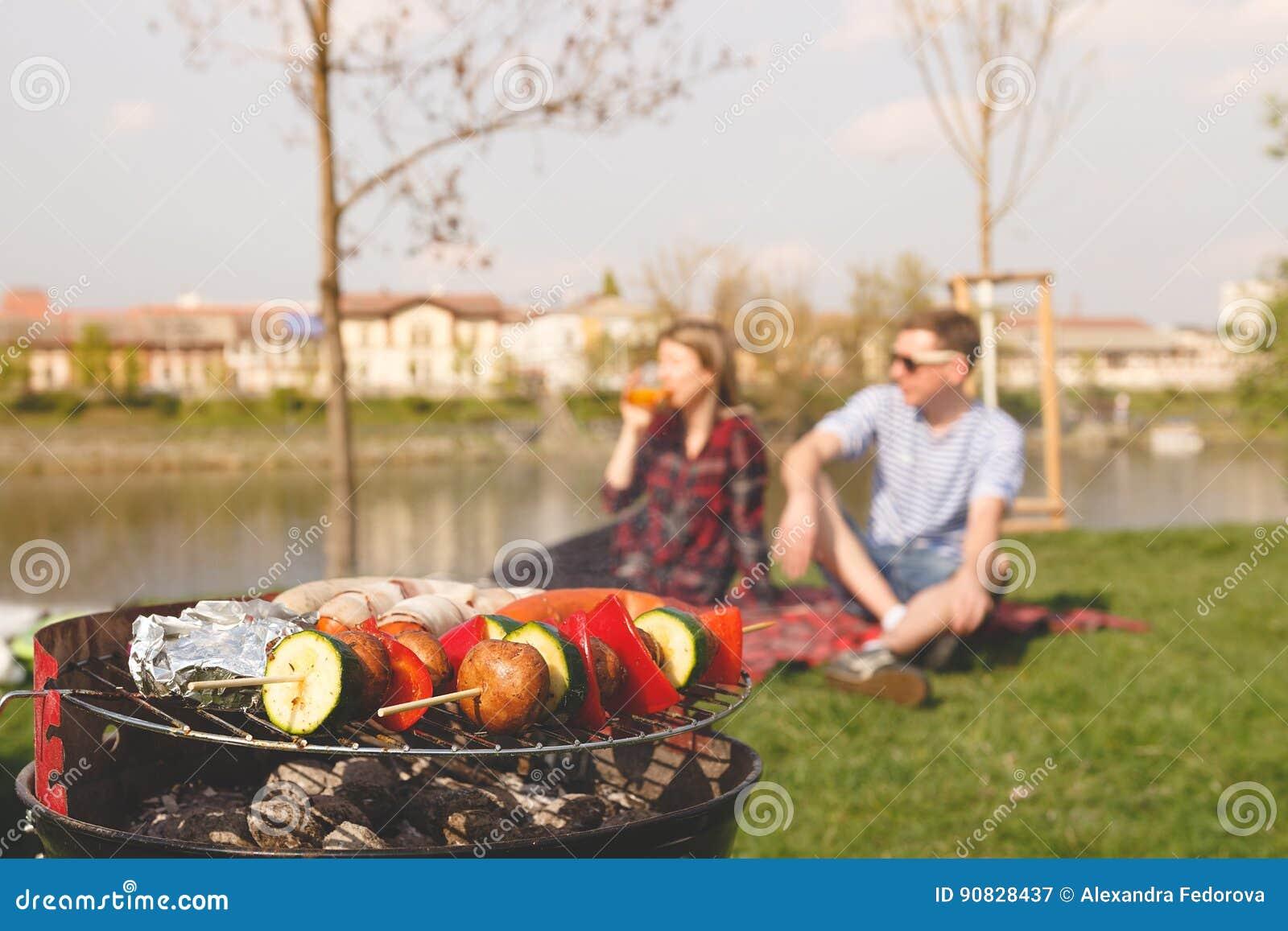 Vrienden die openluchtbarbecue hebben Grill met diverse barbecue, selectieve nadruk