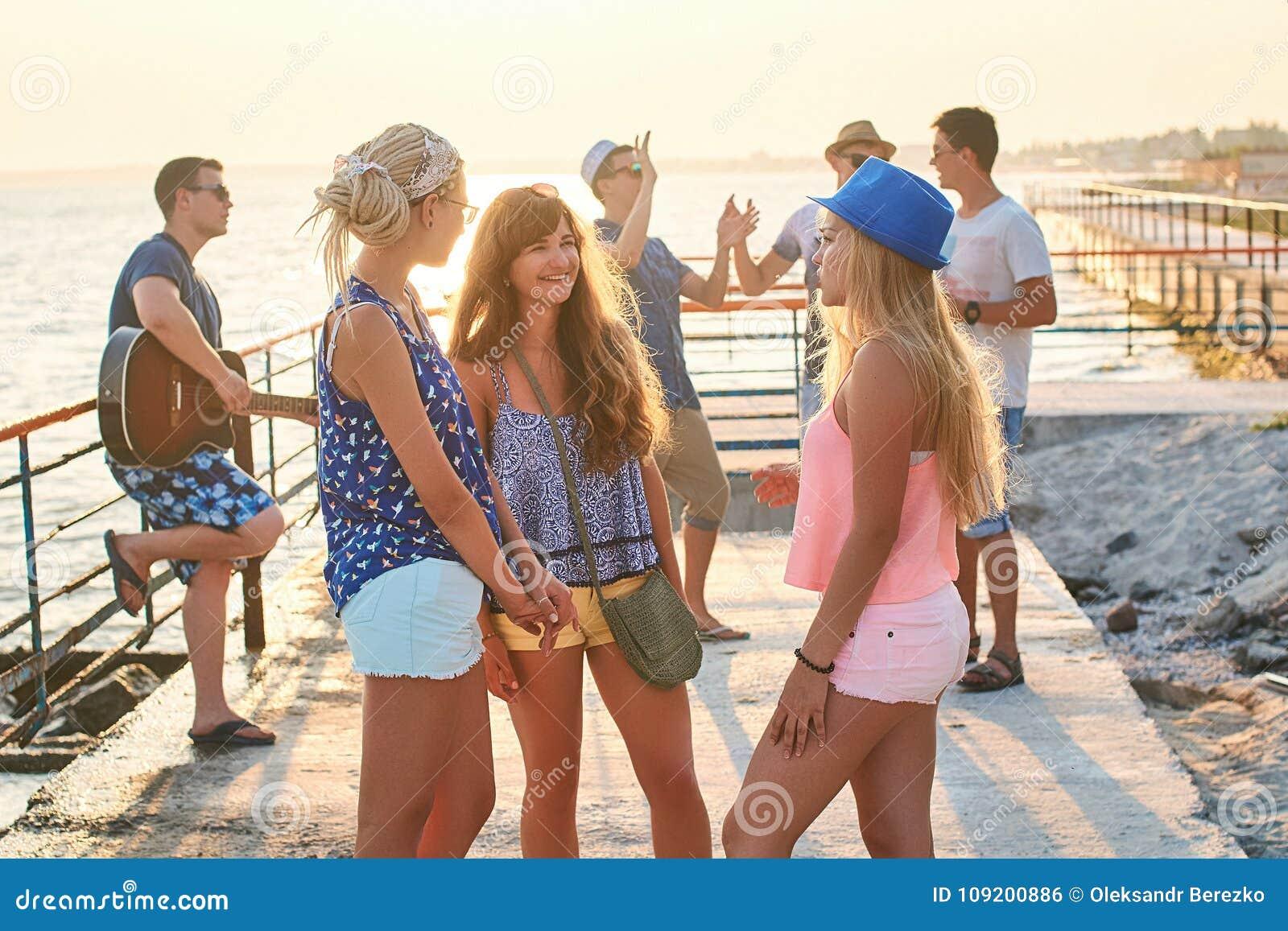 Vrienden die uit bij de zonnige de zomerkust hangen
