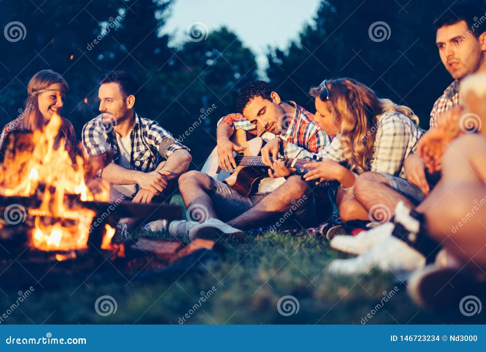 Vrienden die van muziek genieten dichtbij kampvuur bij nacht
