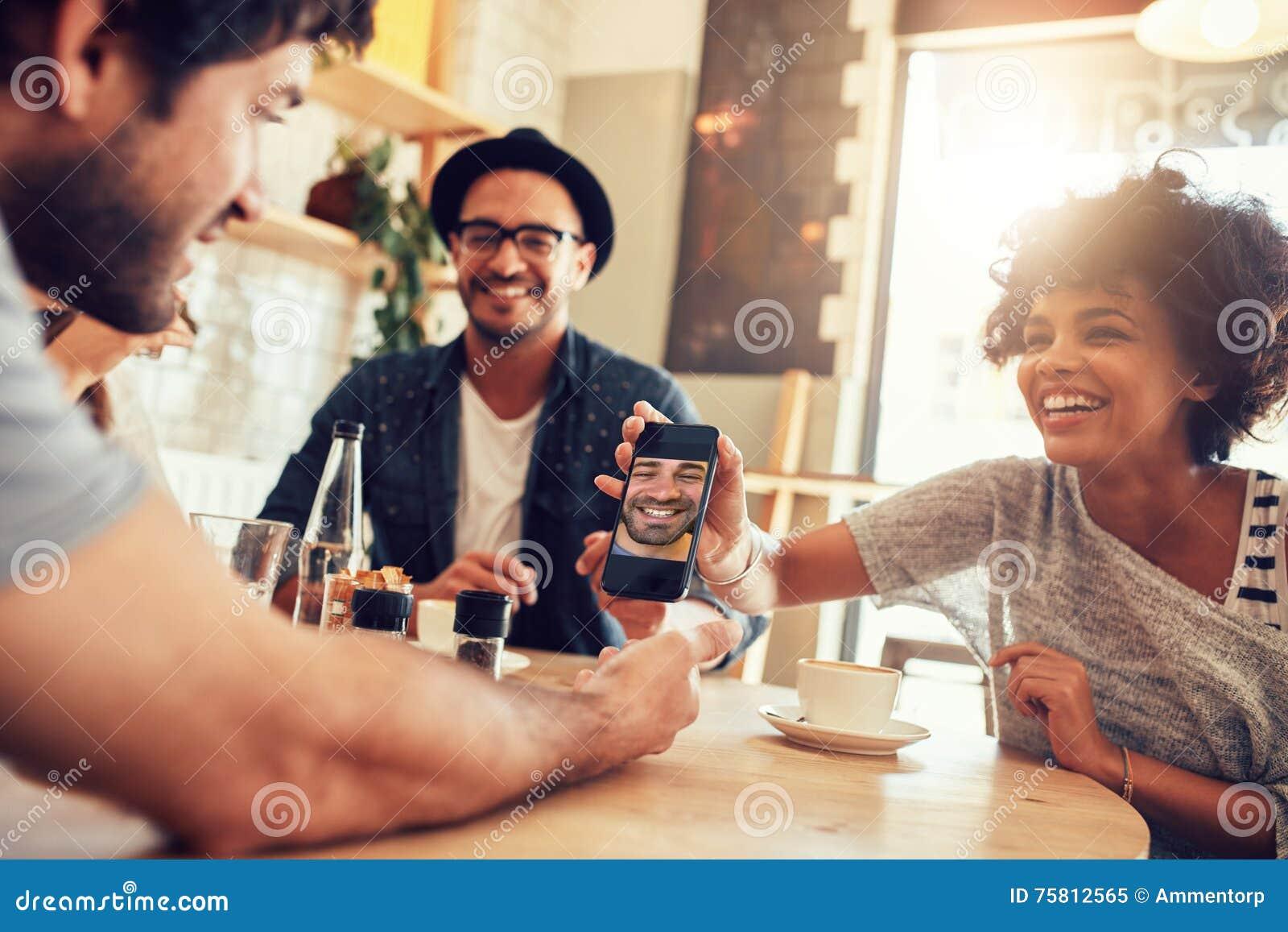 Vrienden in koffie en het bekijken de foto s op slimme telefoon