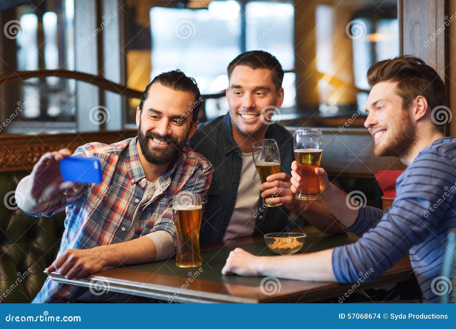 Vrienden selfie en het drinken bier die bij bar nemen