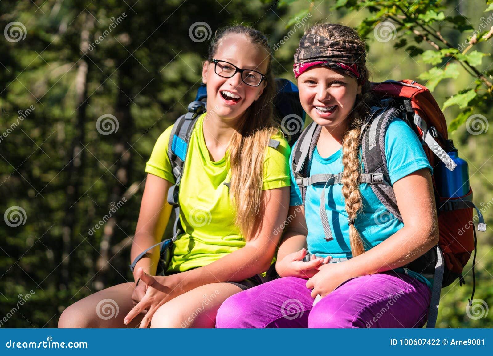 Vrienden of zusters die in het hout wandelen die pret hebben