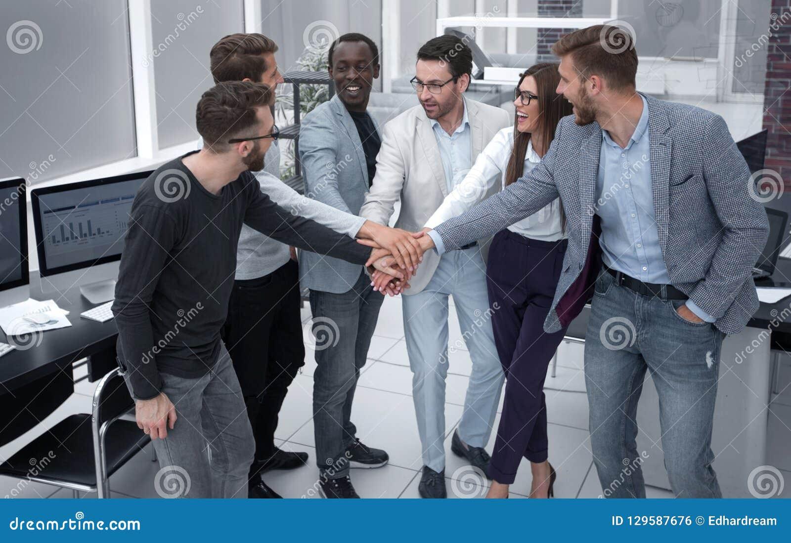 Vriendschappelijk commercieel team die hun handen samenbrengen