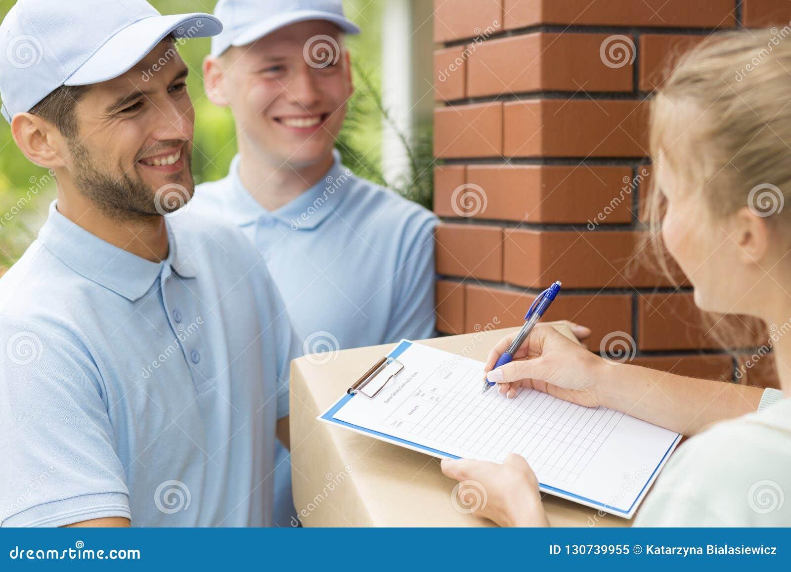 Vriendschappelijke koeriers in blauwe uniformen en vrouw die ontvangstbewijs van pakketlevering ondertekenen