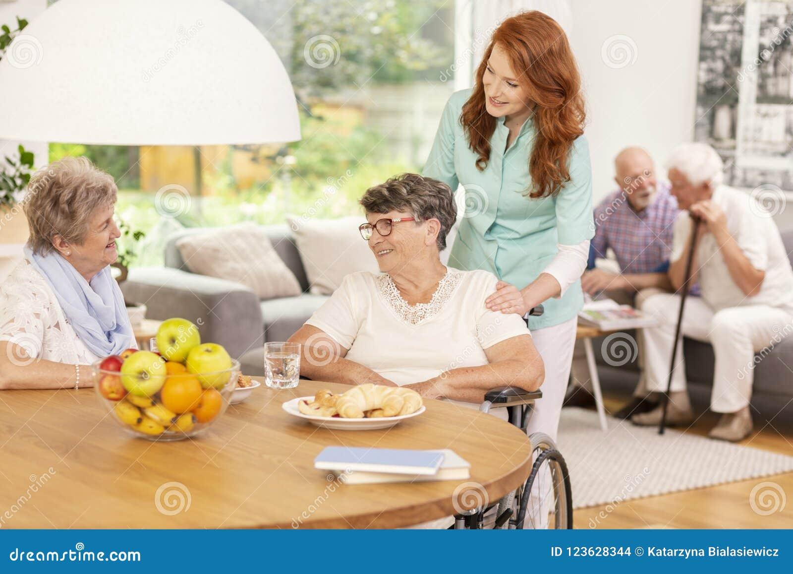 Vriendschappelijke verpleegster ondersteunend gehandicapte zieke vrouw in een rolstoel du