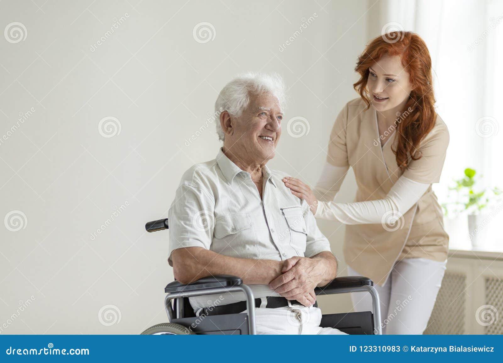Vriendschappelijke verpleegsters ondersteunende glimlachende verlamde hogere mens in een whee