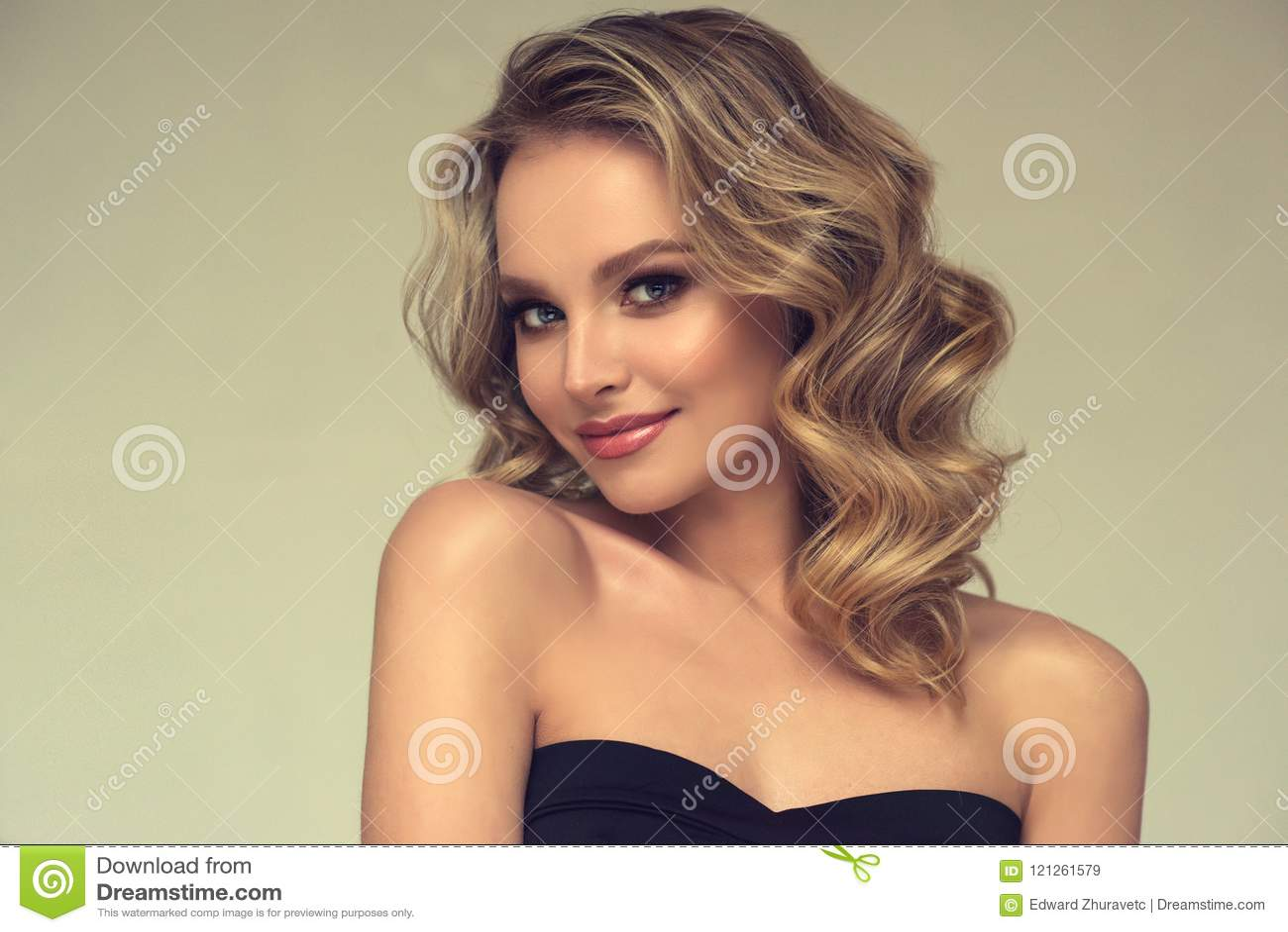 Vrij blond-haired model met krullend, los kapsel en aantrekkelijke make-up