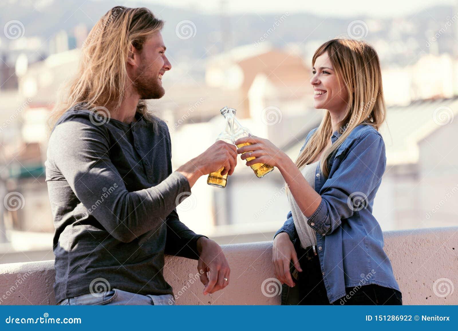 Vrij het jonge paar roosteren met flessenbier terwijl het kijken thuis elkaar op het dak