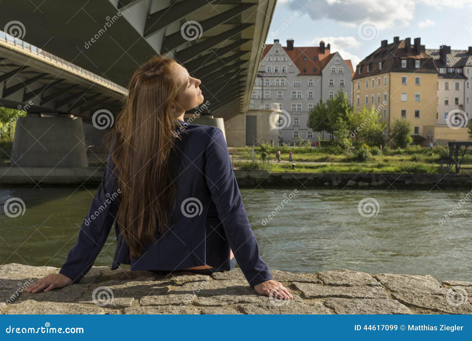 Vrij het jonge vrouw ontspannen bij stedelijke rivieroever