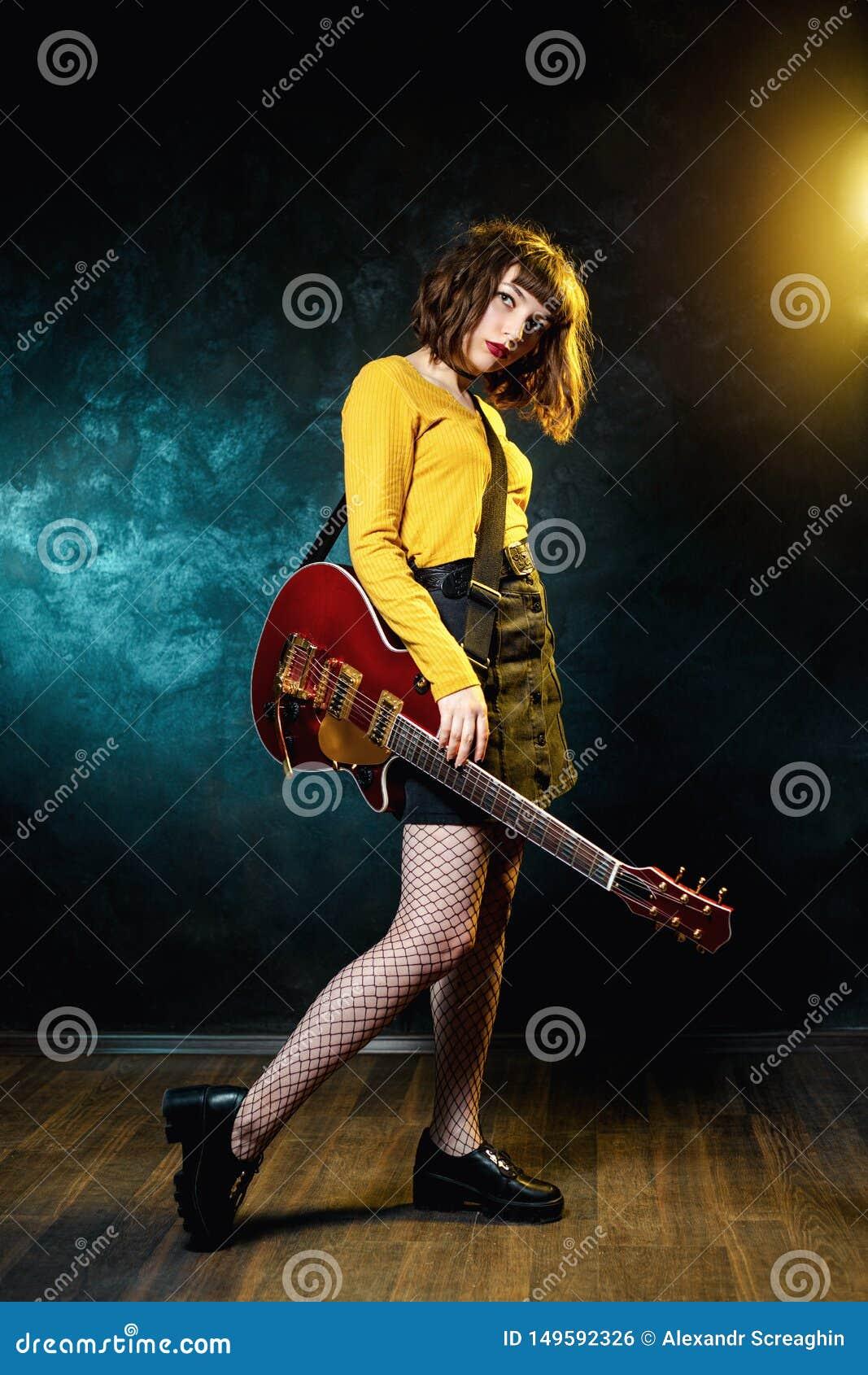 Vrij jonge hipstervrouw met krullend haar met rode gitaar in neonlichten De musicus van de rots speelt elektrogitaar