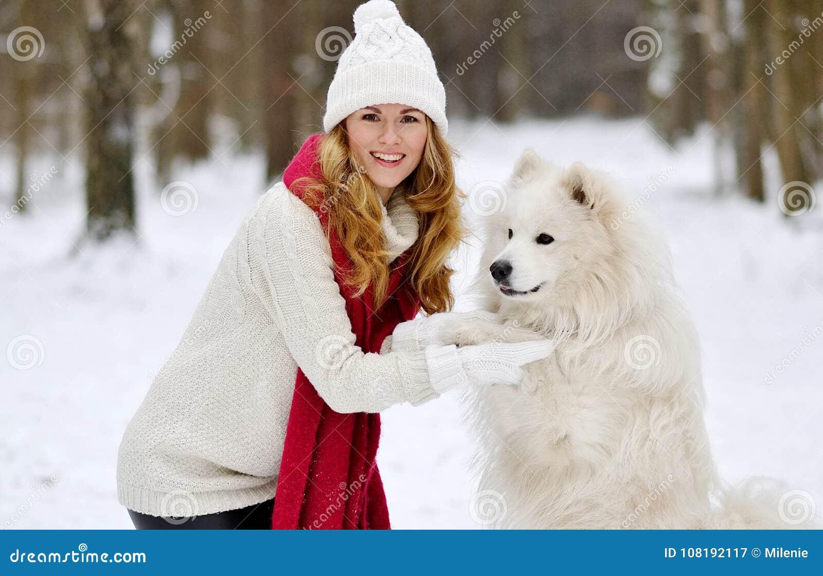 Vrij Jonge Vrouw in de Winter Forest Walking met haar Hond Witte Samoyed