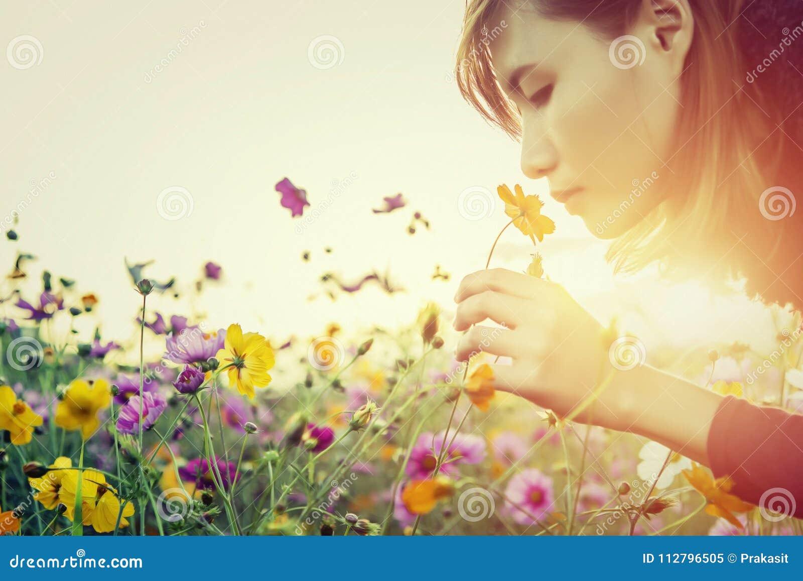 Vrij jonge vrouw die de bloemen ruiken