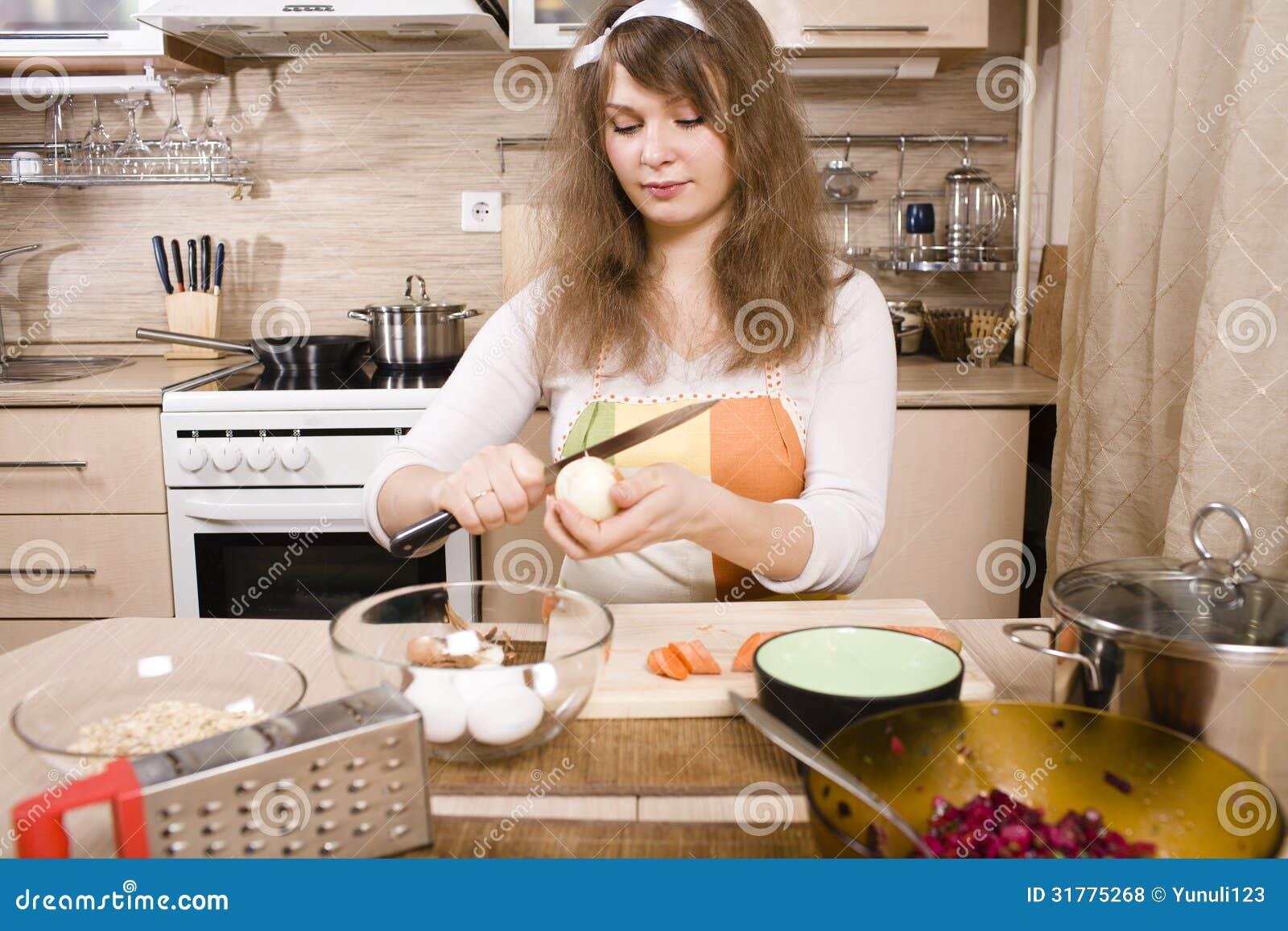 Vrij jonge vrouw die op keuken diner voorbereiden
