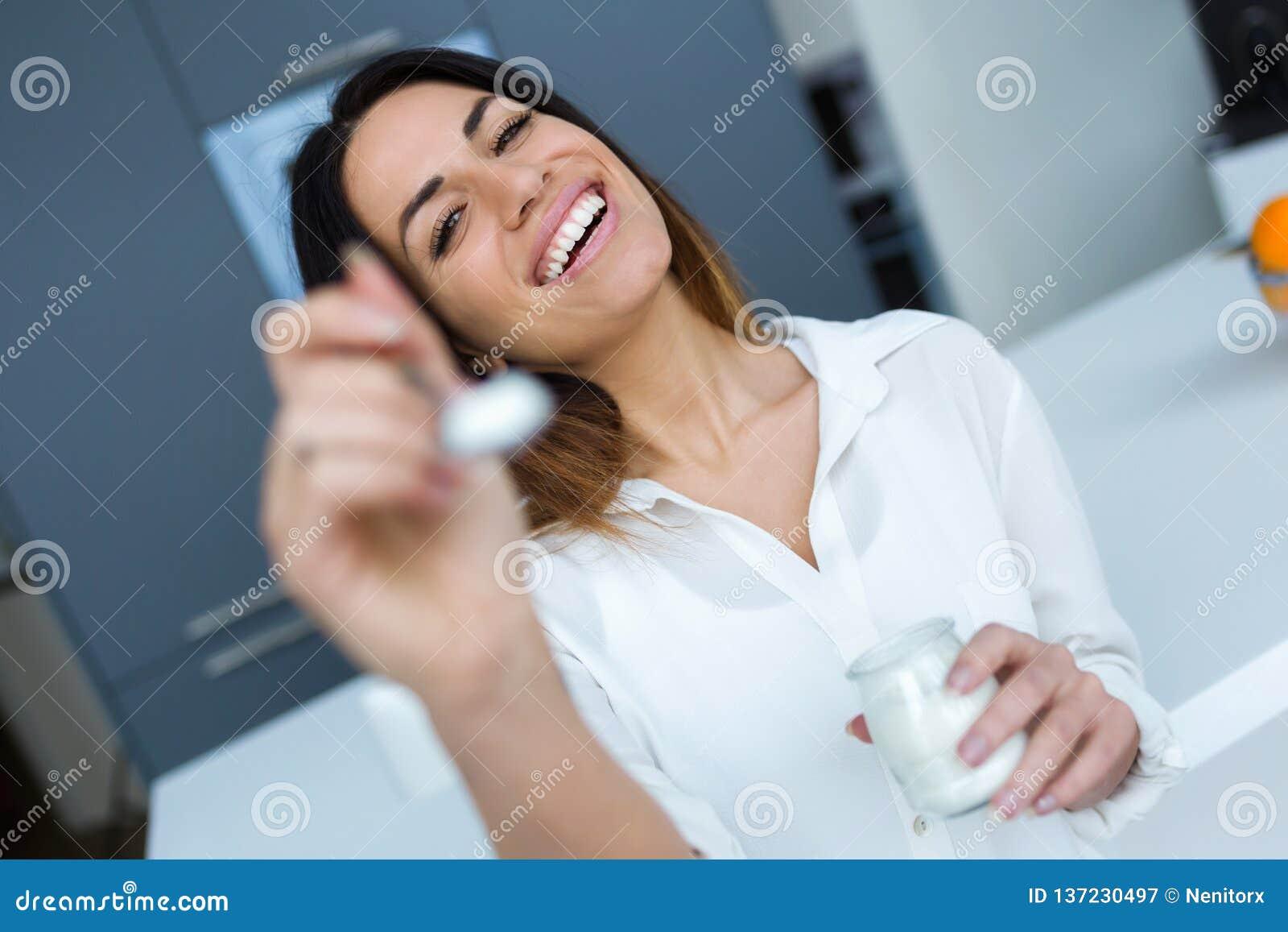 Vrij jonge vrouw die yoghurt tonen aan camera terwijl thuis het eten in de keuken
