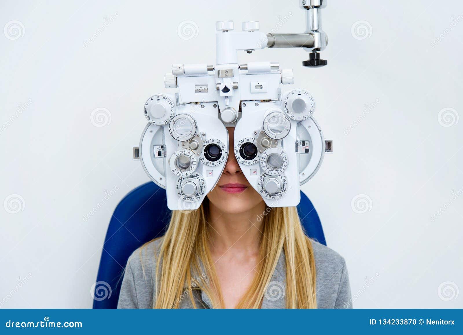 Vrij jonge vrouw die zichtmeting met optische phoropter in oftalmologiekliniek doen