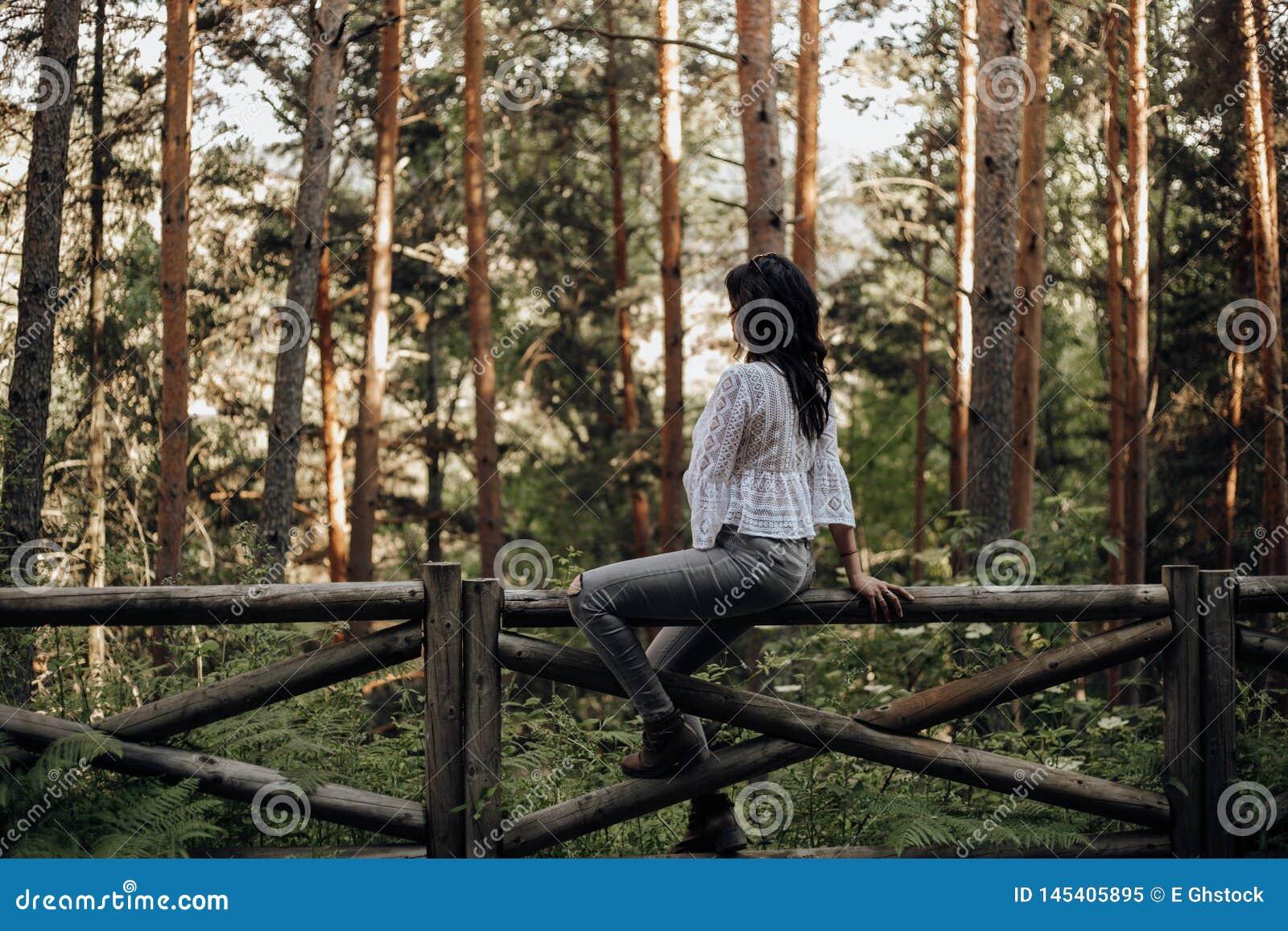 Vrij jonge vrouw met intense blik onder palmen