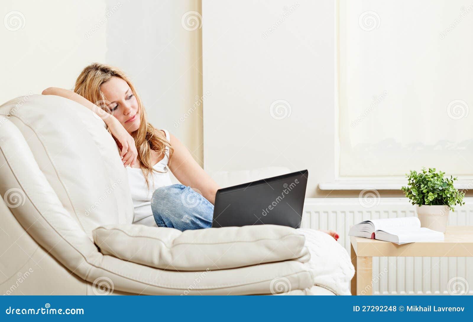 Vrij jonge vrouwenzitting op sifa met laptop