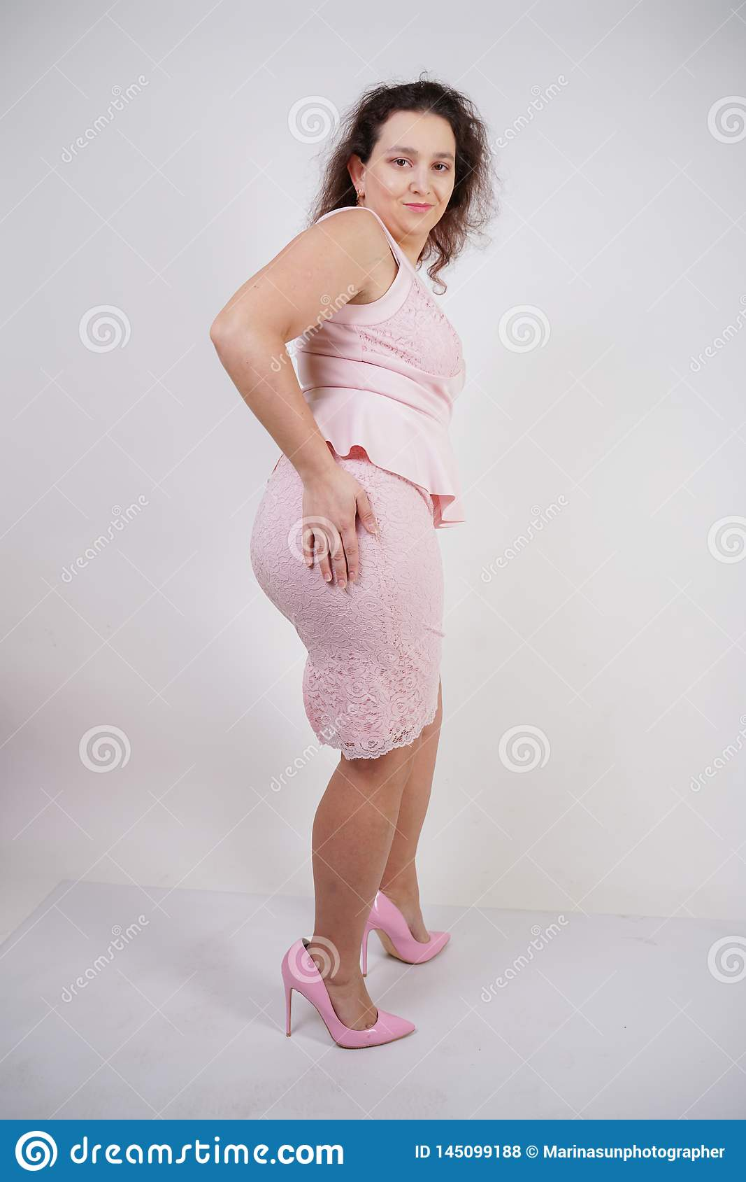 Vrij mollig positief meisje die in roze modieuze kleding op witte studioachtergrond dansen