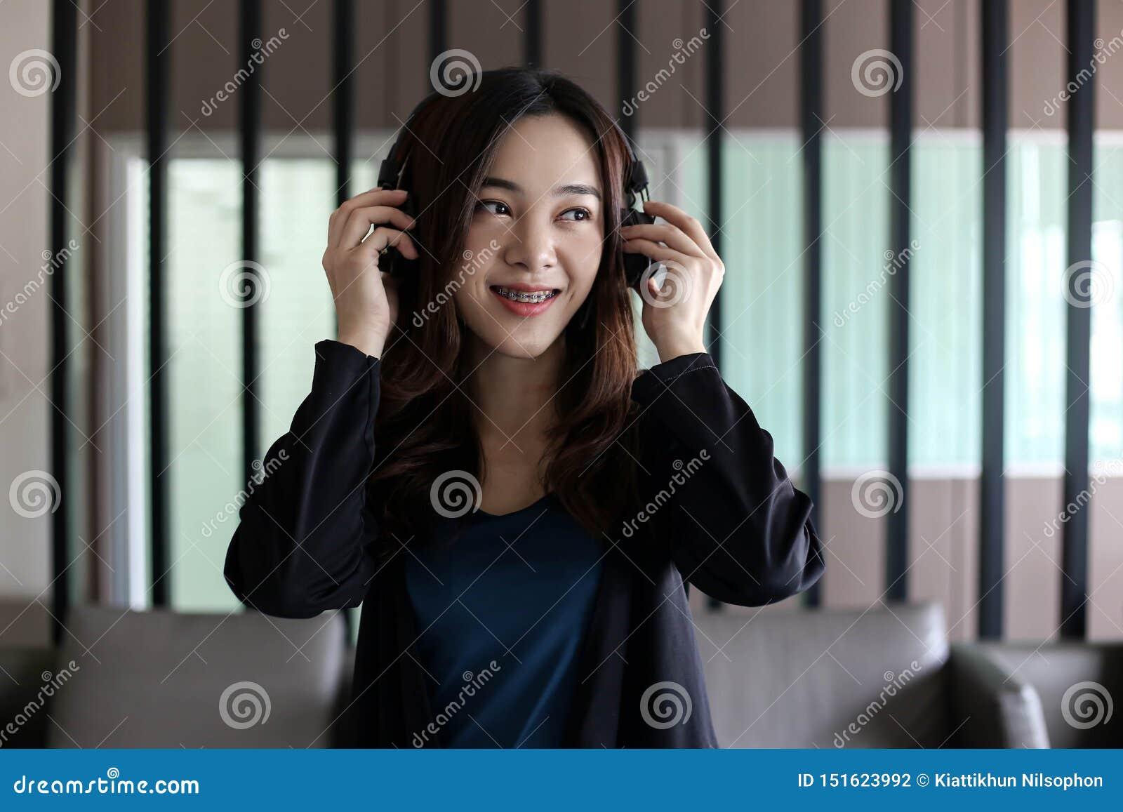 Vrij mooie Aziatische vrouw die hoofdtelefoon en het luisteren muziek dragen