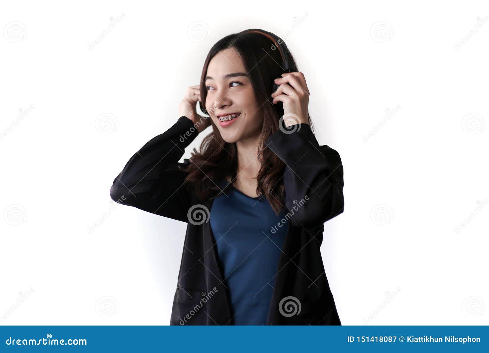 Vrij mooie Aziatische vrouw die hoofdtelefoon en het luisteren muziek op witte achtergrond dragen