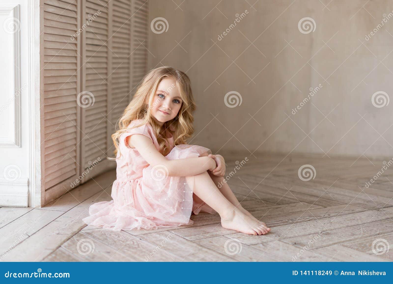 Vrij mooie meisjeszitting op de vloer en het glimlachen Binnenfoto Het meisje van Nice