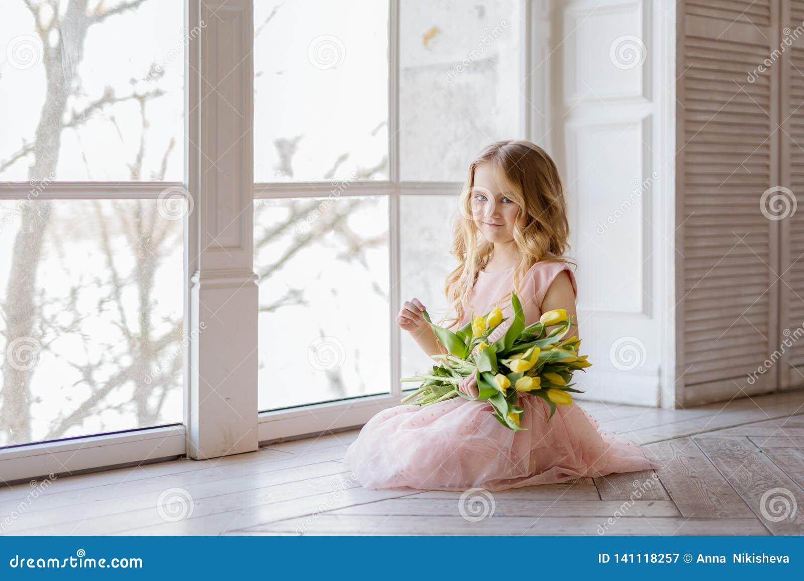 Vrij mooie meisjeszitting op de vloer met gele bloemen tulpen en het glimlachen Binnenfoto Het meisje van Nice De ruimte van het