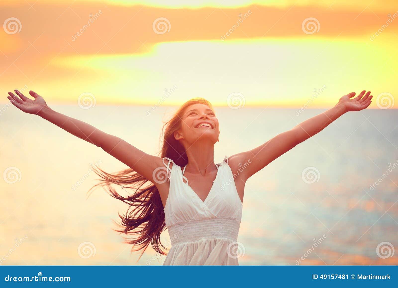 Vrije gelukkige vrouw die vrijheid prijzen bij strandzonsondergang