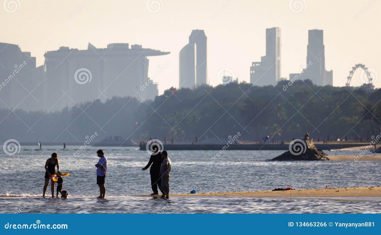 Vrije tijdsbeeld van mensen enjoysthe strand met centrale het districtsgebouwen van Singapore