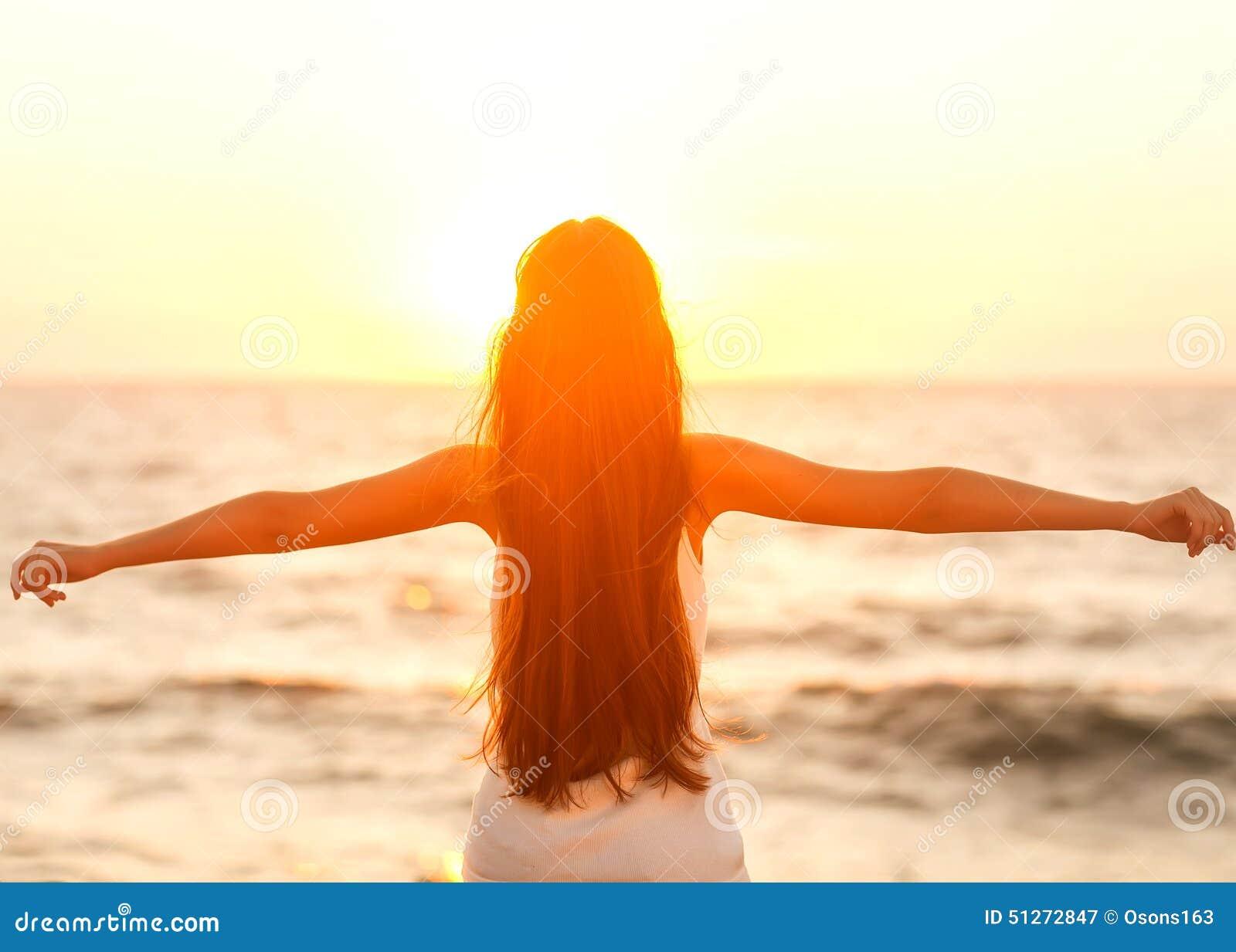 Vrije vrouw die van vrijheid genieten die gelukkig bij strand bij zonsondergang voelen Ben