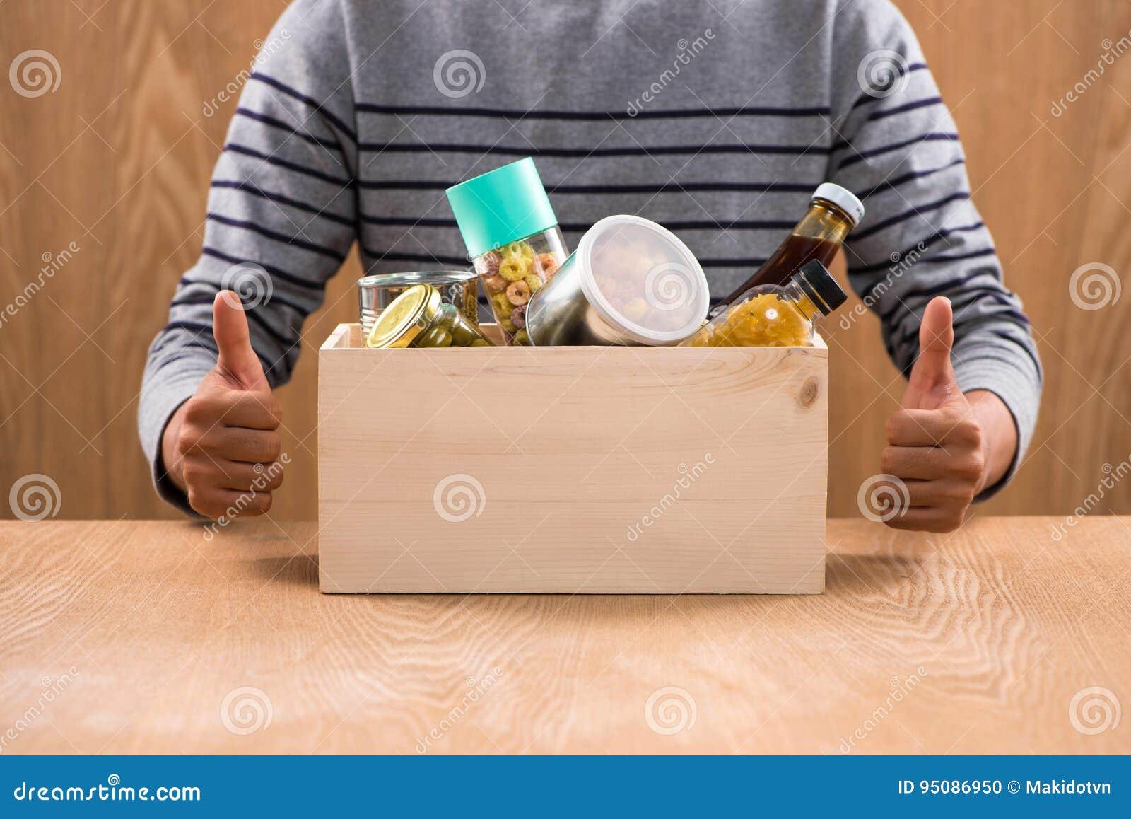 Vrijwilliger met schenkingsdoos met levensmiddelen op houten achtergrond
