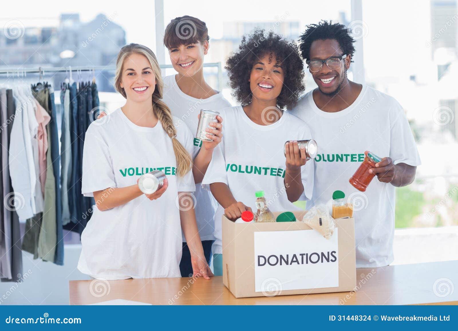 Vrijwilligers die voedsel van een schenkingsdoos nemen