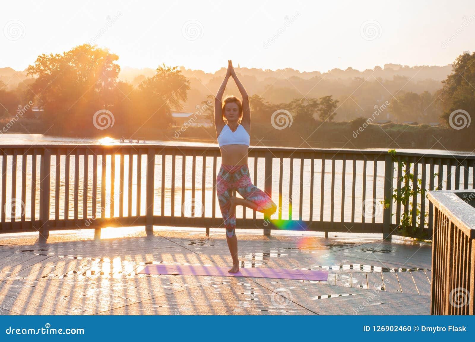 Vrikshasana pose. Young woman is doing yoga on the sunrise