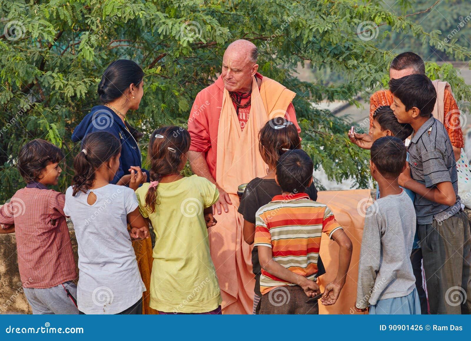 Vrindavan, 22 October 2016: Hare Krishna monk surrounded by Indian children, in Vrindavan, UP