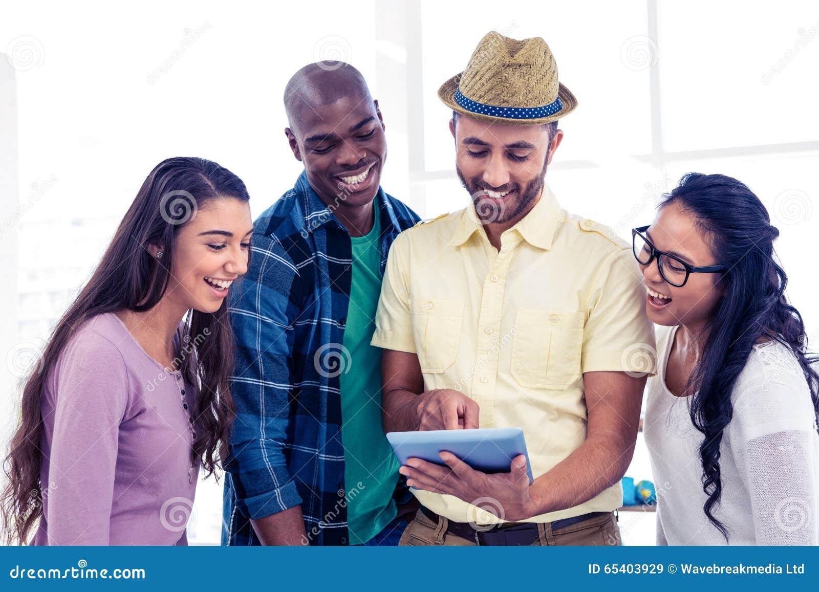 Vrolijk creatief team die tabletpc met behulp van