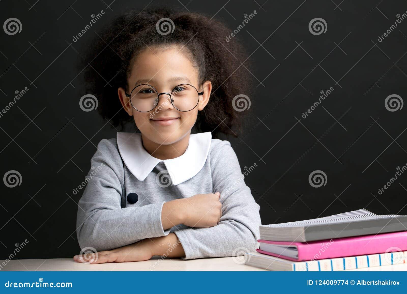Vrolijk jong geitje met lange golvende pluizige zwarte haarzitting in het klaslokaal