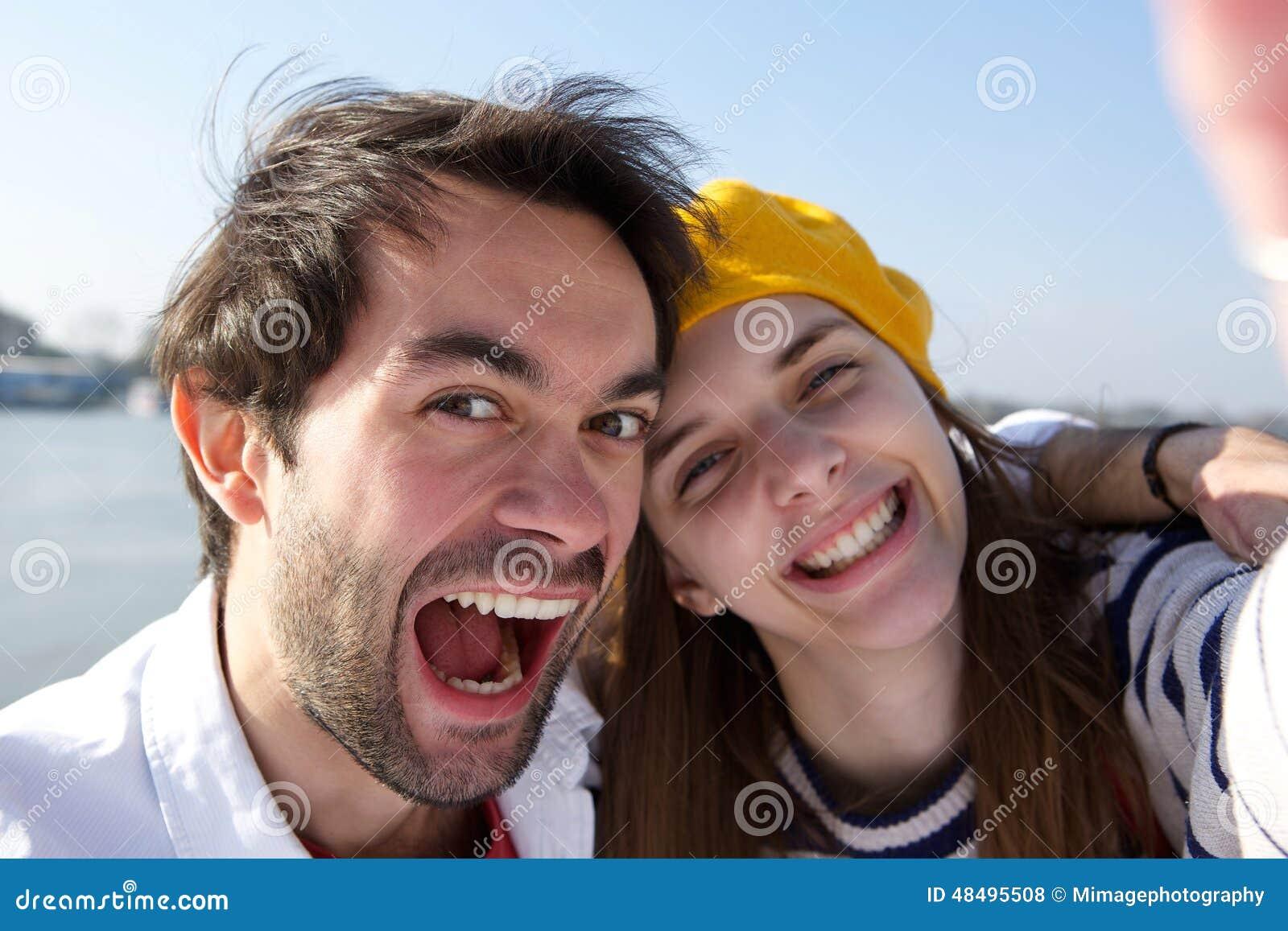 Vrolijk jong glimlachend paar die selfie nemen