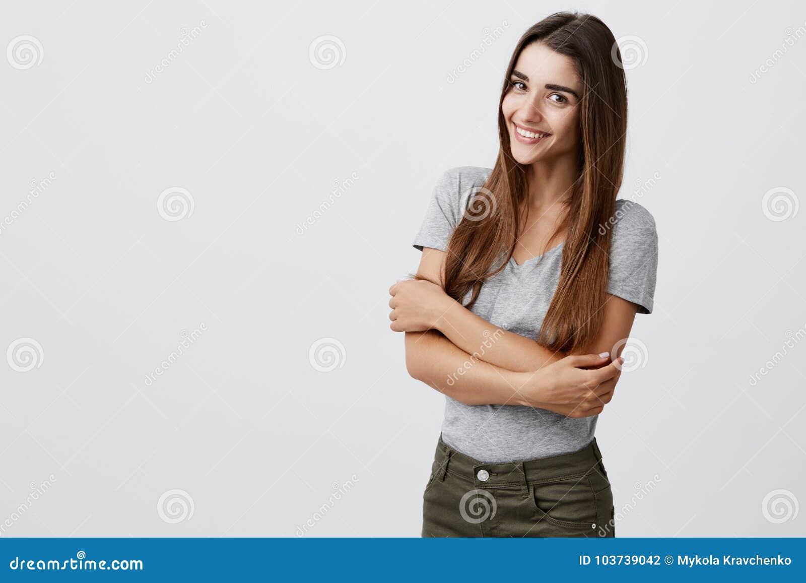 Vrolijk jong mooi donkerbruin Kaukasisch studentenmeisje die met lang haar in toevallige modieuze uitrusting helder glimlachen