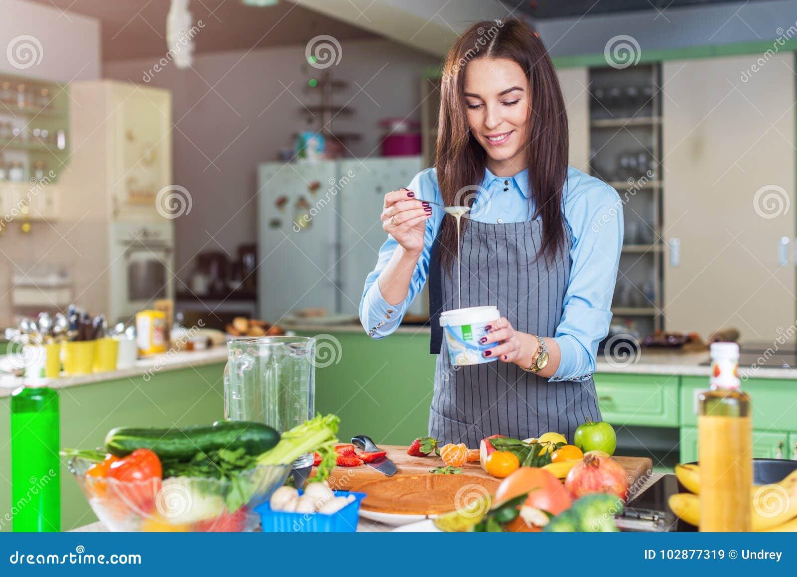 Vrolijk jong vrouwelijk chef-kok kokend dessert die condens in schotel in haar keuken toevoegen