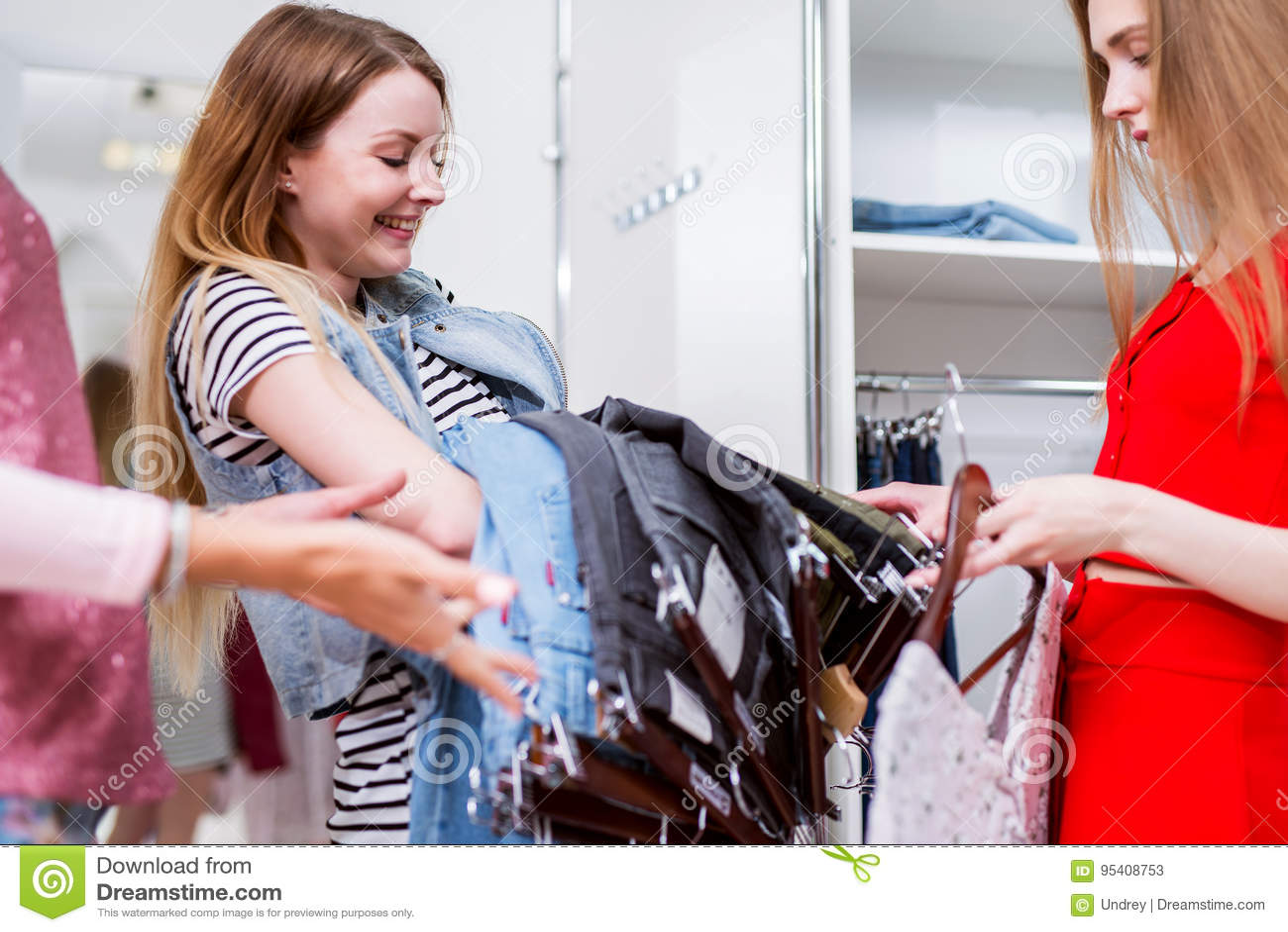 Vrolijk Kaukasisch meisje die of jeans met een winkelmedewerker kopen kiezen in een kledingsopslag